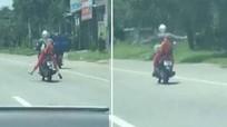 Người phụ nữ vừa lái xe máy vừa buông hai tay tập thể dục