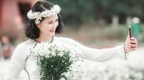 Hoa khôi bóng chuyền Kim Huệ tạo dáng bên hoa xuân