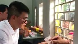 Công Vinh mặc sơ mi trắng, đeo kính hiệu ngồi bán vé vào sân Thống Nhất