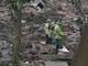 Người chồng băng qua đống đổ nát của kho phế liệu đưa vợ đi cấp cứu
