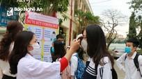 Đi học sau kỳ nghỉ dài, học sinh Nghệ An được đo thân nhiệt và dùng nước sát khuẩn miễn phí