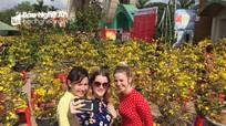 Du khách Tây diện áo dài chụp ảnh với hoa Tết