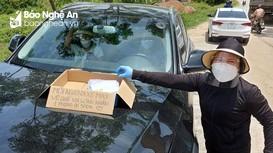 Người phụ nữ ở Nghệ An phát phong bì tiền cho người dân về quê tránh dịch bằng xe máy