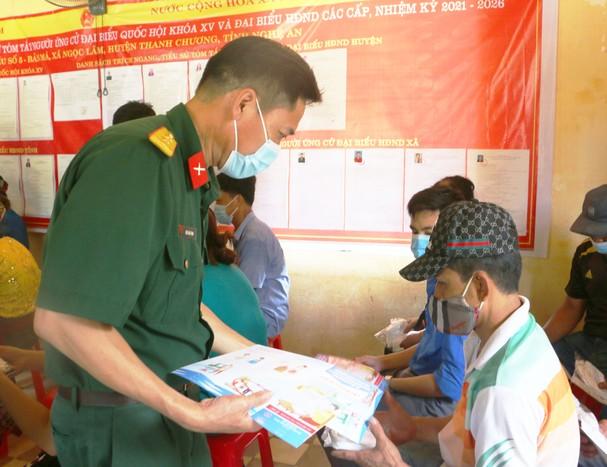 Bộ đội biên phòng đang phát khẩu trang, tờ rơi đến tay những người dân bản Mà, xã Ngọc Lâm. Ảnh: An Quỳnh.