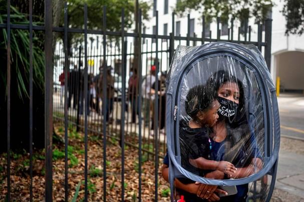 Dana Clark và cậu con trai 18 tháng tuổi Mason xếp hàng chờ đợi để bỏ phiếu sớm cho cuộc bầu cử tổng thống ở New Orleans, Louisiana ngày 16/10. Clark cho biết cô trùm túi nhựa bảo vệ vì không biết có bao nhiêu người sẽ đeo khẩu trang khi xếp hàng. Ảnh: Reuters