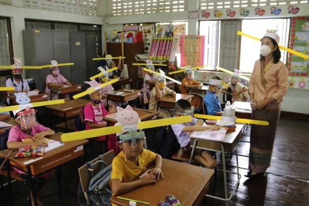 Giáo viên và học sinh đeo khẩu trang và mặt nạ chống giọt bắn để phòng dịch Covid-19,tại trường Ban Pa Muad ở Chiang Mai, Thái Lan. Ảnh: AP