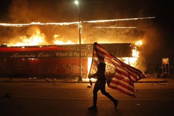 Một người biểu tình cầm ngược lá cờ Mỹ, một dấu hiệu của sự đau khổ, bên cạnh một tòa nhà đang bốc cháy vào ngày 28/5 ở Minneapolis, sau khi cảnh sát ghì chết George Floyd. Ảnh: AP