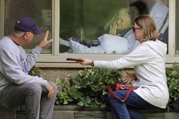 Judie Shape (ở giữa) mắc Covid-19, chào những người con của mình qua cửa kính tại Trung tâm chăm sóc ở Kirkland, Washington. Ảnh: AP