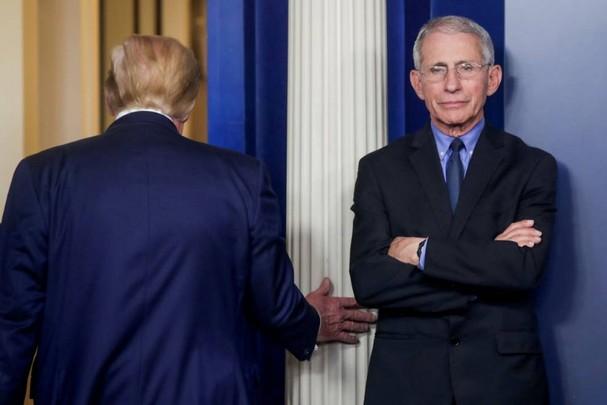 Tổng thống Trump rời đi sau khi phát biểu trong cuộc họp giao ban hàng ngày của lực lượng chống Covid-19. Bên cạnh ông Trump là Tiến sĩ Anthony Fauci, Giám đốc Viện Quốc gia về Dị ứng và Bệnh truyền nhiễm. Ảnh: Reuters