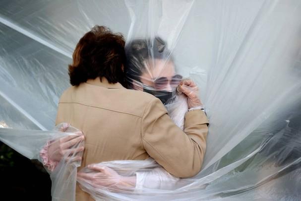 Olivia Grant ôm bà của mình, Mary Grace Sileo, qua một tấm vải nhựa ở Wantagh, New York ngày 24/5. Đây là lần đầu tiên họ gặp nhau kể từ khi đợt bùng phát dịch Covid-19 vào cuối tháng 2. Ảnh: Getty Images